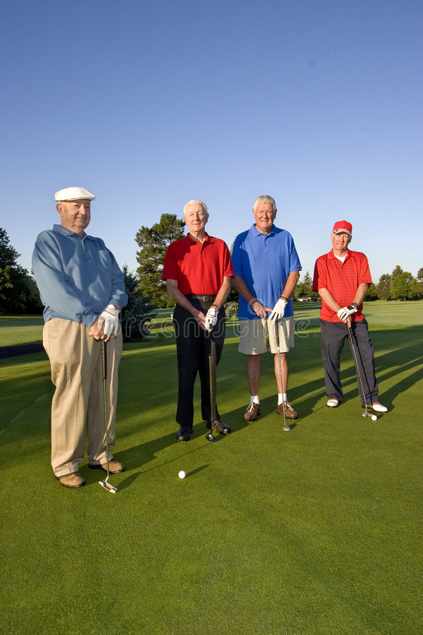 Men on Course with Clubs. Four elderly men are standing together on a golf course. They are holding their clubs, smiling, and looking at the camera. Vertically royalty free stock image