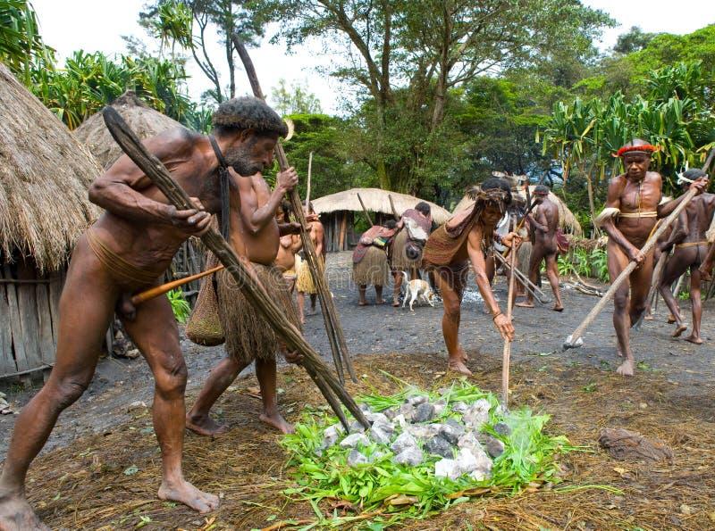 Men Dani tribe in the village are the hot stones for cooking meat. DANI VILLAGE, WAMENA, IRIAN JAYA, NEW GUINEA, INDONESIA – 15 MAY 2012: Men Dani tribe royalty free stock photo