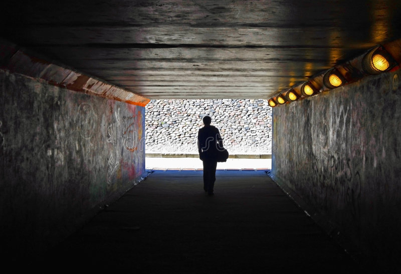 Men in the dark tunnel stock photo