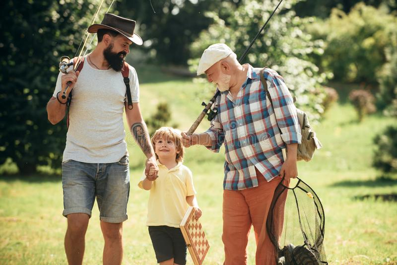 Men day. Happy grandfather, father and grandson with fishing rods. Anglers. Men day. Happy grandfather, father and grandson with fishing rods. Anglers stock photos