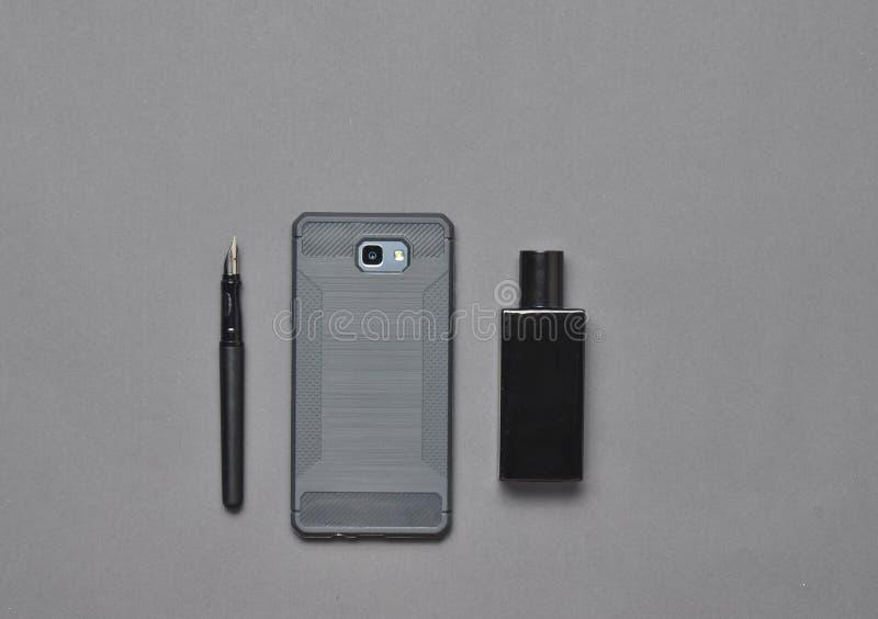 Men' disposição dos acessórios do negócio de s em uma superfície cinzenta Vista superior Pena, smartphone, garrafa de perfum imagens de stock