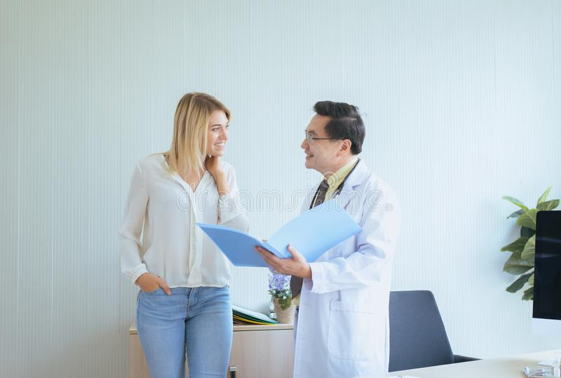 Man doctor examining to happy woman patient and follow up treatment at hospital royalty free stock photography