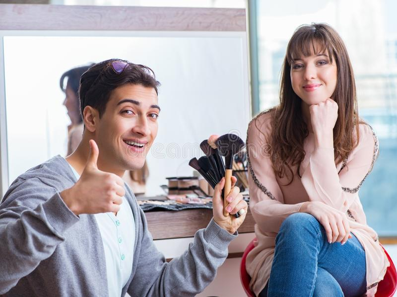 Man doing make-up for cute woman in beauty salon. The men doing make-up for cute women in beauty salon stock photography