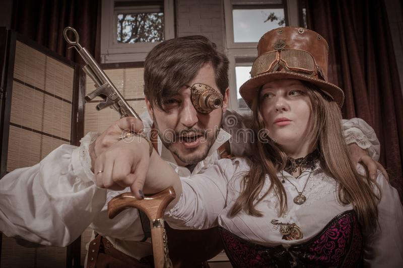 A man is doing a tattoo for a woman, vintage steampunk royalty free stock photography