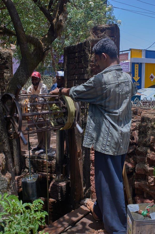 Men drawing water from a well in mahabaleshwar street.Sahyadri range of Maharashtra royalty free stock photo