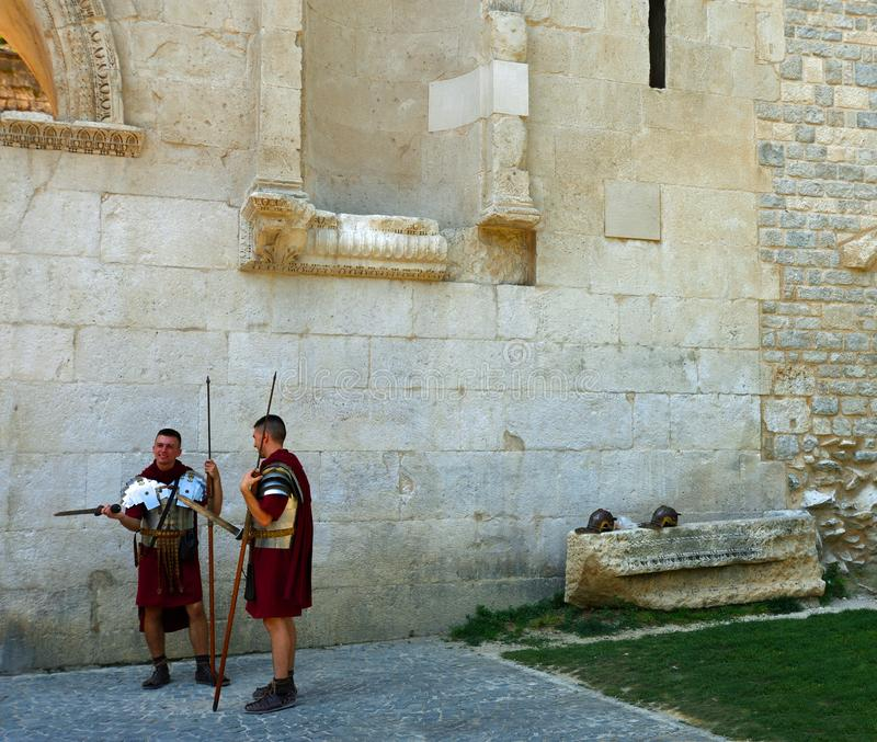 Men dressed as Roman Soldiers by historic Palace Wall. royalty free stock photography