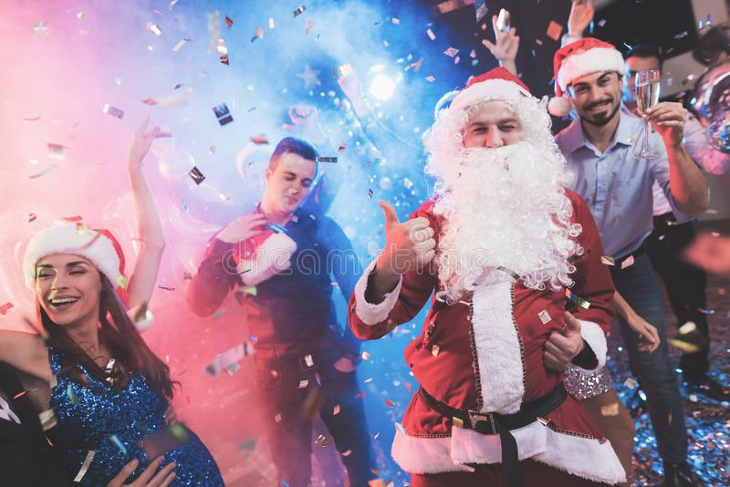 A man dressed as Santa Claus has fun at a New Year party. Together with him have fun friends. stock photography