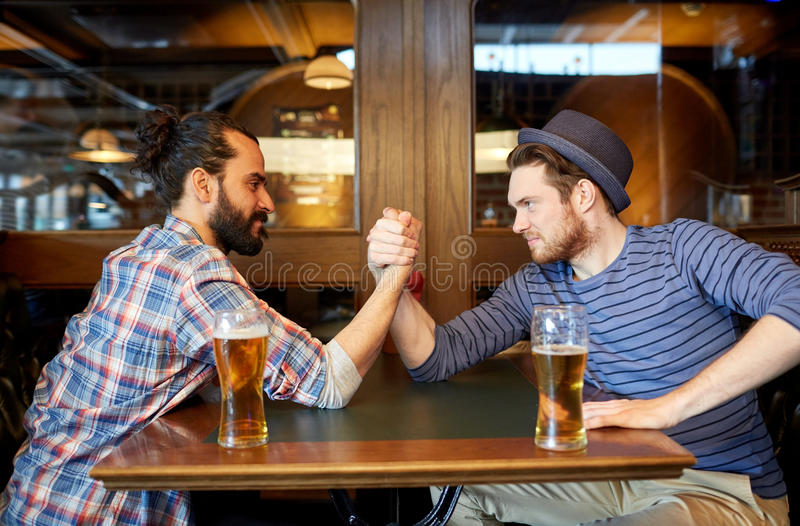 Men drinking beer and arm wrestling at bar or pub. People, leisure, friendship and party concept - happy male friends drinking draft beer and arm wrestling at royalty free stock images