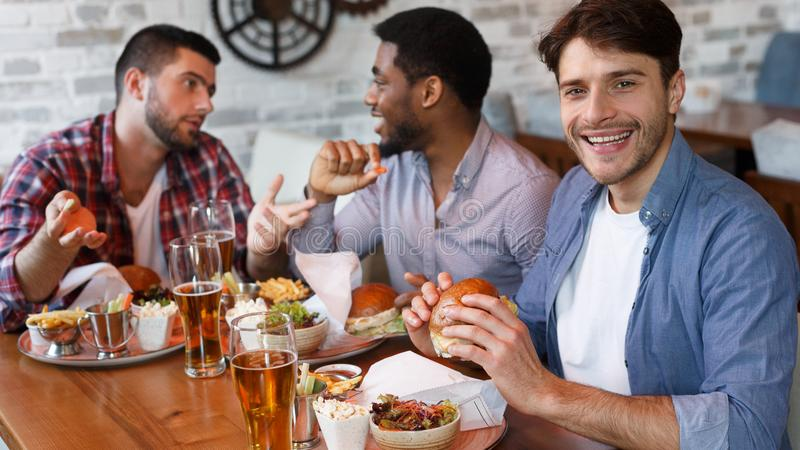 Men Eating Burgers And Drinking Beer In Bar. stock photography