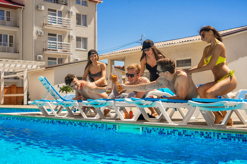 Men enjoy a massage from women near the swimming pool. Party at smimming pool. Cheers. Men enjoying a massage from women near the swimming pool. They drink beer royalty free stock photography