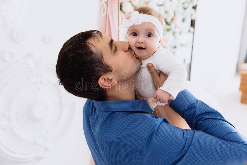 A man enjoys fatherhood and kisses his little daughter with tenderness and love. The baby is amazed at the daddy`s. A men enjoys fatherhood and kisses his little royalty free stock photography