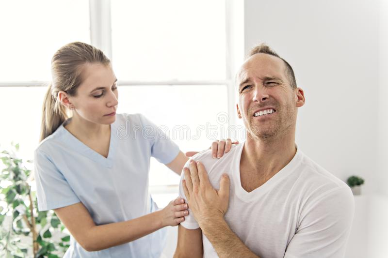 Men Explaining Shoulder injury to the doctor royalty free stock images