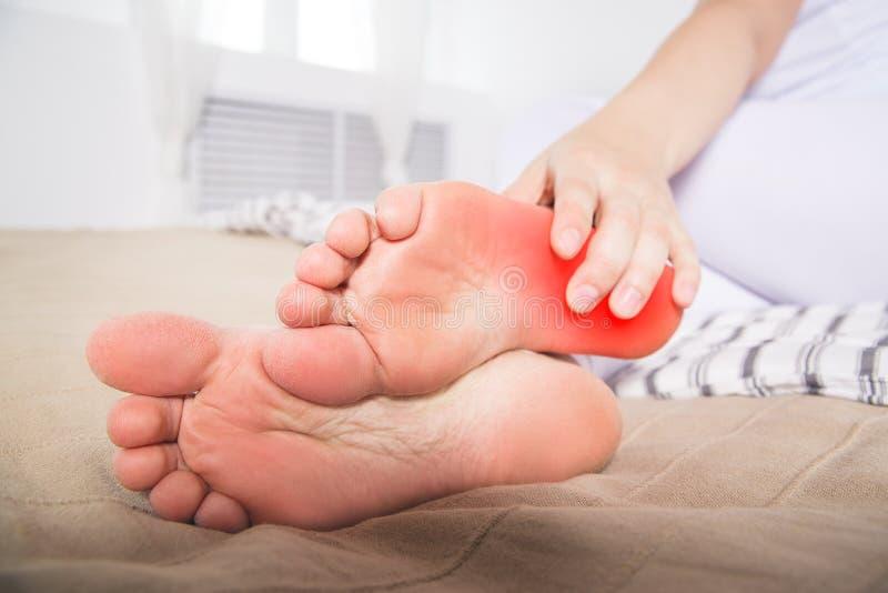 Men för ben för kvinna` s, smärtar i hälet, massage av kvinnlig fot arkivfoto