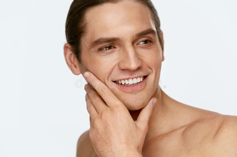Men Face Care. Man Touching Smooth Skin After Shaving. On White Background. High Resolution stock images