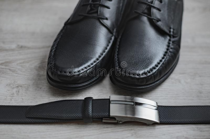 Men fashion. Men accessories. Black shoes and black belt . Still life. Business look on a wooden background stock photo