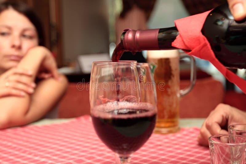 The men fills red wine stock image
