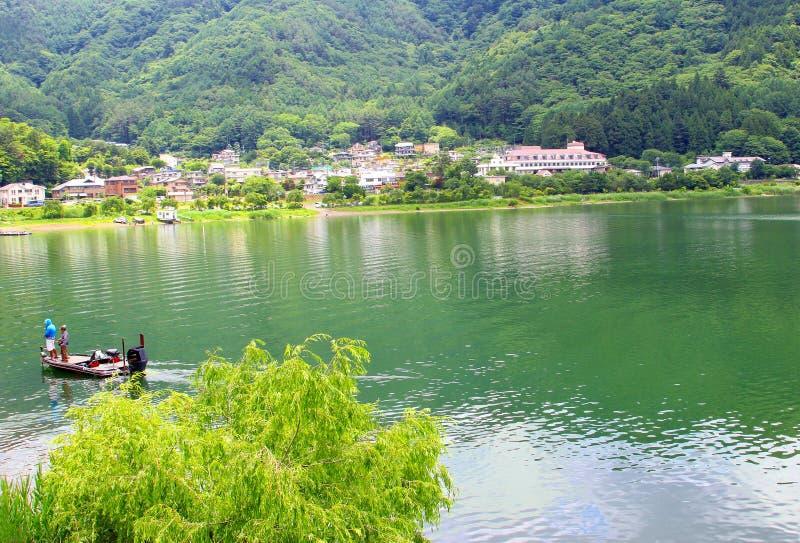 June 2018, Men fishing boat Lake Kawaguchiko water mountains, Japan stock photos