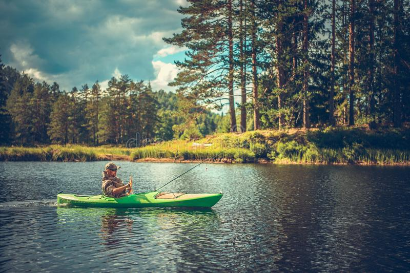 Men Fishing From a Kayak. Caucasian Men in His 30s Fishing From a Kayak. Lake Recreation Time royalty free stock photography