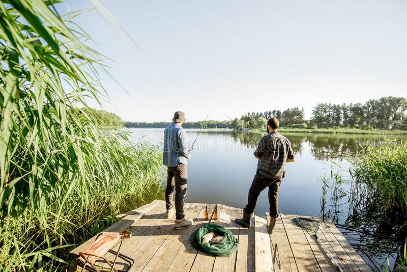 Men fishing on the lake. Landscape view on the beautiful lake and green reeds with two men fishing on the wooden pier during the morning light royalty free stock photo