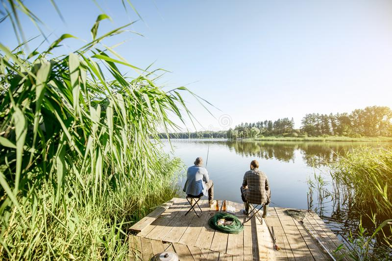Men fishing on the lake. Landscape view on the beautiful lake and green reeds with two men fishing on the wooden pier during the morning light royalty free stock image