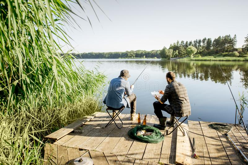 Men fishing on the lake. Landscape view on the beautiful lake and green reeds with two men fishing on the wooden pier during the morning light royalty free stock photography