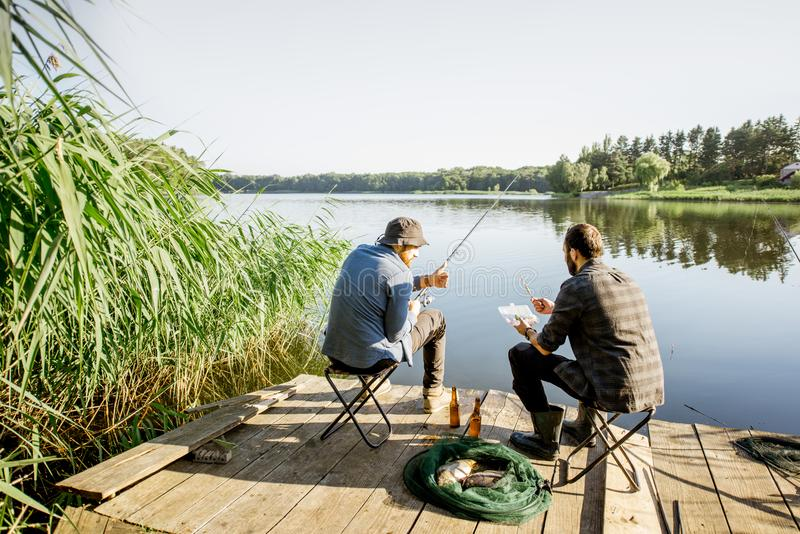Men fishing on the lake. Landscape view on the beautiful lake and green reeds with two men fishing on the wooden pier during the morning light stock photos