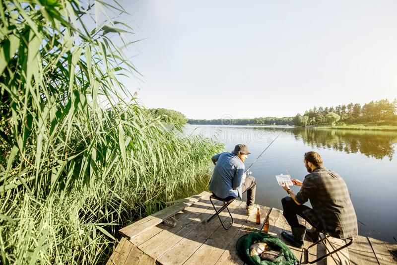 Men fishing on the lake. Landscape view on the beautiful lake and green reeds with two men fishing on the wooden pier during the morning light stock photography