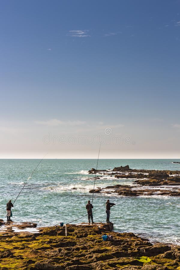 Men fishing off the rocks of Paseo Fernando Quinones in Cadiz royalty free stock image