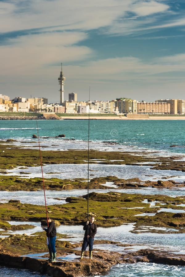 Men fishing off the rocks of Paseo Fernando Quinones in Cadiz stock photos