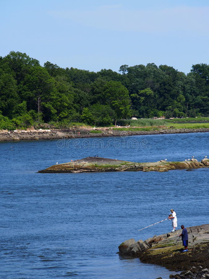 Men fishing at Pelham Bay Park , Bronx NY. Pelham Bay Park is a popular fishing spot for local residents . Large Bluefish and stripers are just some of the fish stock photos