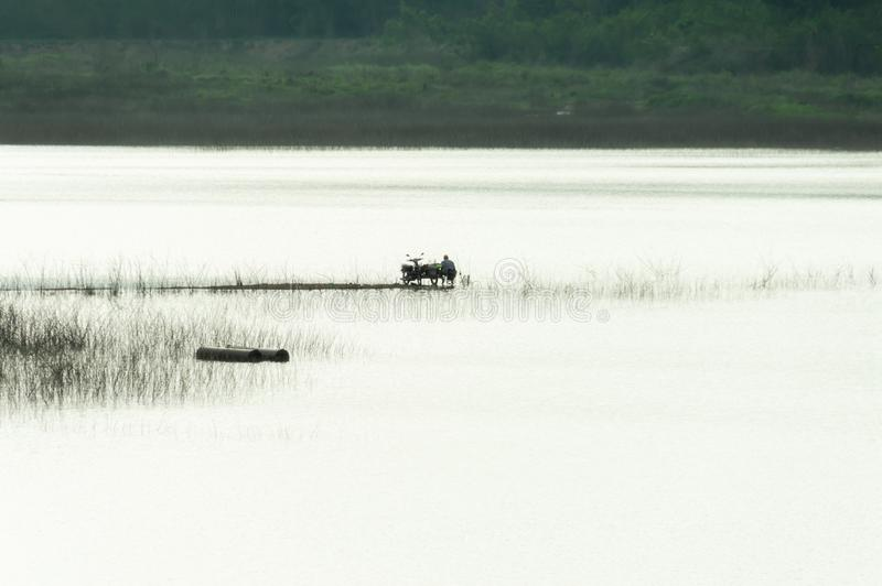 Men are fishing  at The reservoir contains. Landscape images of The reservoir contains sediment that extends into the meddle of the reservoir, where men are royalty free stock images