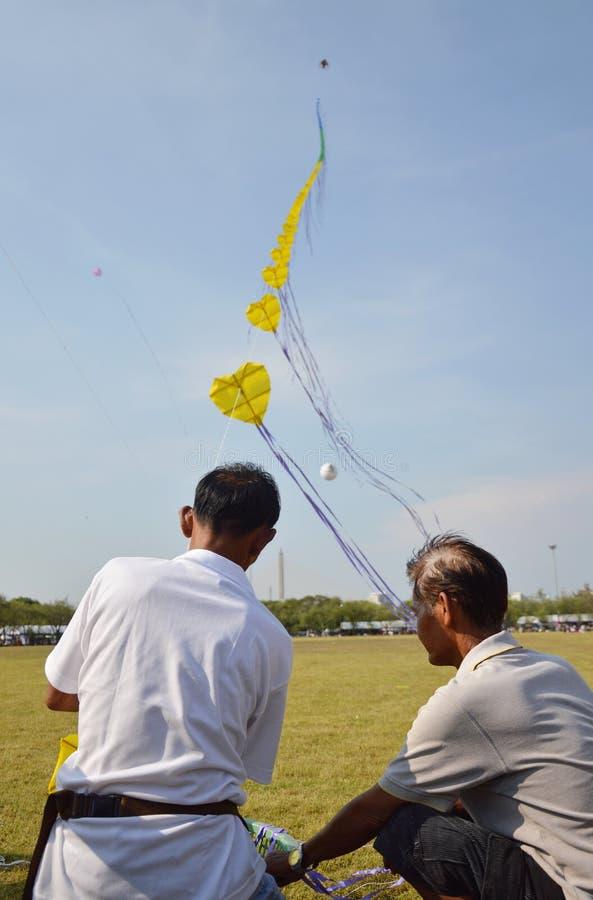 Men fly long rope kite in Bangkok celebration 232 anniversary at Sanam Laung Thailand. Bangkok Thailand April 20, 2014 men fly long rope kite in Bangkok royalty free stock photo