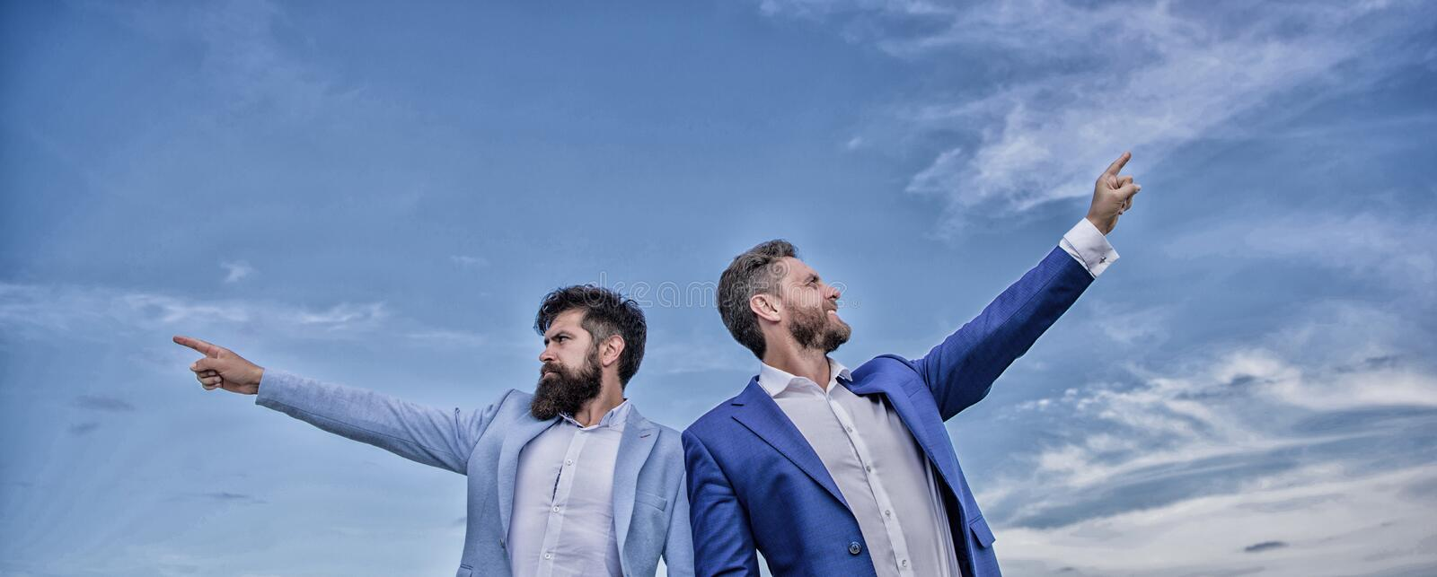 Men formal suit managers pointing at opposite directions. Changing course. New business directions. Developing business stock image