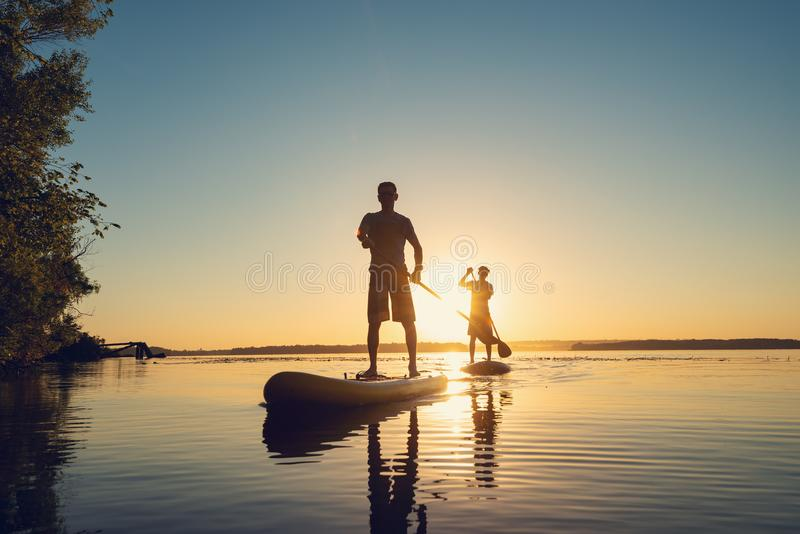 Men, friends sail on a SUP boards in a rays of rising sun. Stand up paddle boarding - awesome active recreation in nature. Backlight royalty free stock photography