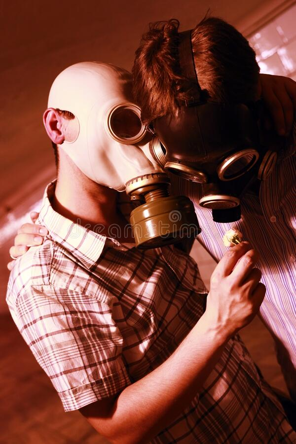 Men in a gas mask on night street. Men in a gas mask with flower on night street royalty free stock image