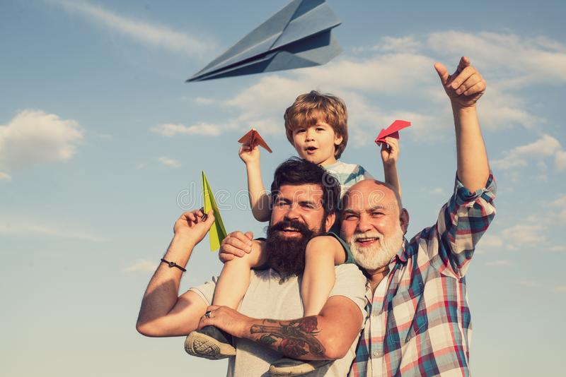 Men generation. Young boy with father and grandfather enjoying together in park on blue sky background. Three men. Generation. Happy men loving family. Dad and stock photography
