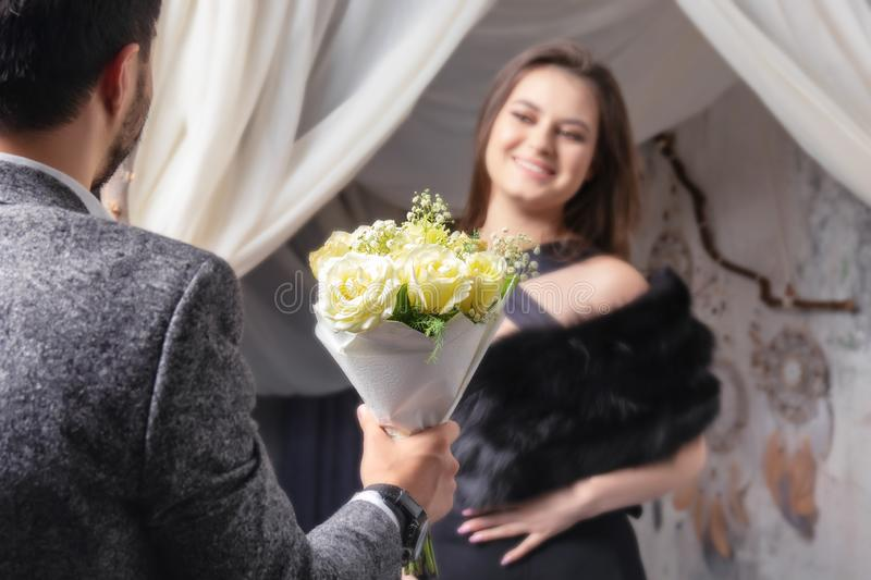 A man gives a bouquet of yellow roses to his beloved woman . stock image