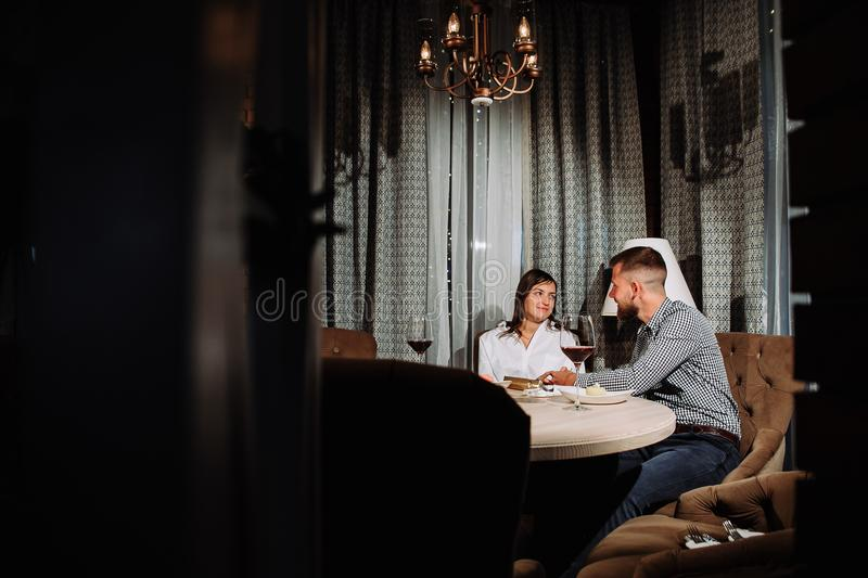 A man gives a gift to his girlfriend on a date in a restaurant royalty free stock images