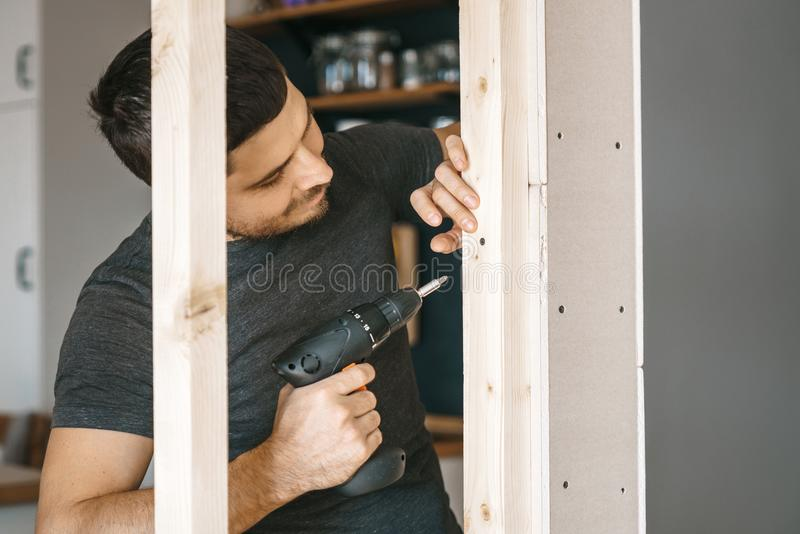 Men in gray clothes work as a screwdriver, fixing a wooden frame for the window to the gypsum plasterboard partition. stock image