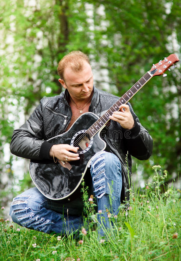 Download Men with guitar stock photo. Image of grass, male, jeans - 14850018