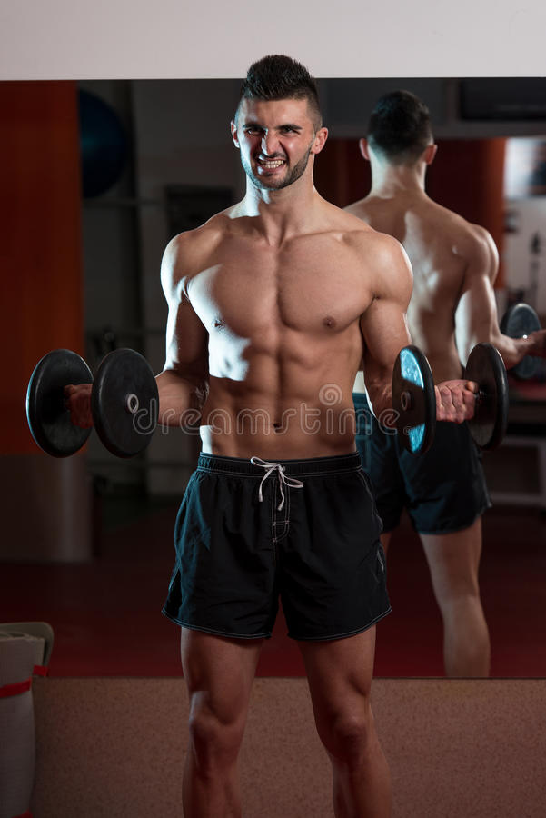 Men In Gym Exercising With Dumbbells. Man In The Gym Exercising Biceps With Dumbbells royalty free stock images