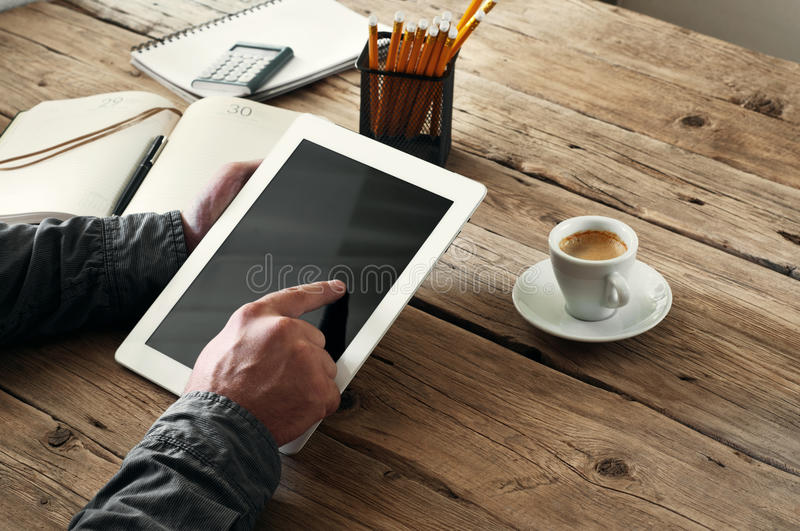 Men hand clicks on the tablet screen on wooden background royalty free stock image