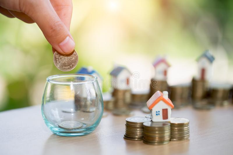 A men hand holding stacking gold coins and house model, saving m. Oney for buying a new home and investment with real estate concept stock images
