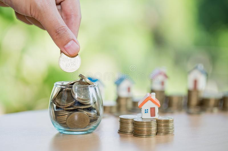 A men hand holding stacking gold coins and house model, saving m. Oney for buying a new home and investment with real estate concept stock image