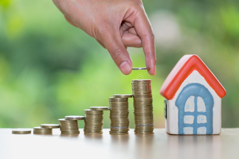 A men hand holding stacking gold coins and house model, saving m. Oney for buying a new home and investment with real estate concept royalty free stock image