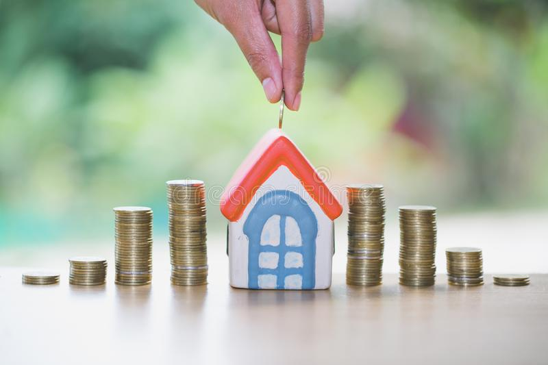 A men hand holding stacking gold coins and house model, saving money for buying a new home and investment with real estate concept.  royalty free stock images