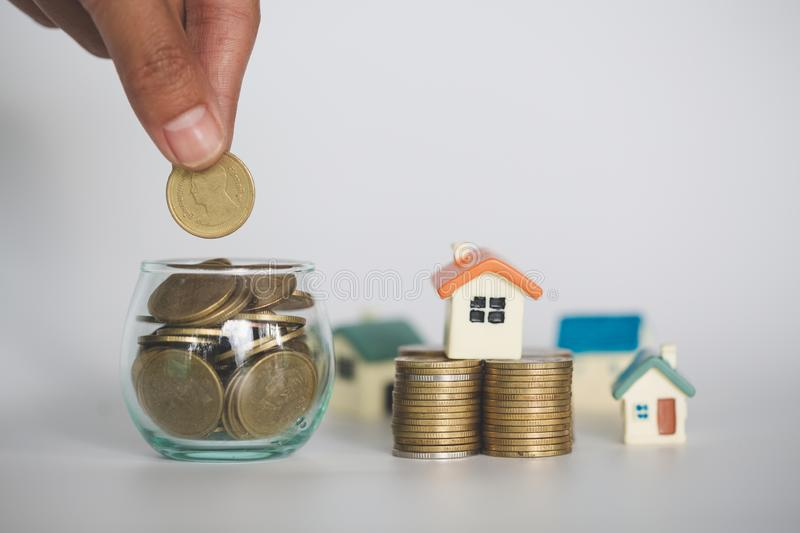 A men hand holding stacking gold coins and house model, saving money for buying a new home and investment with real estate concept.  royalty free stock photography