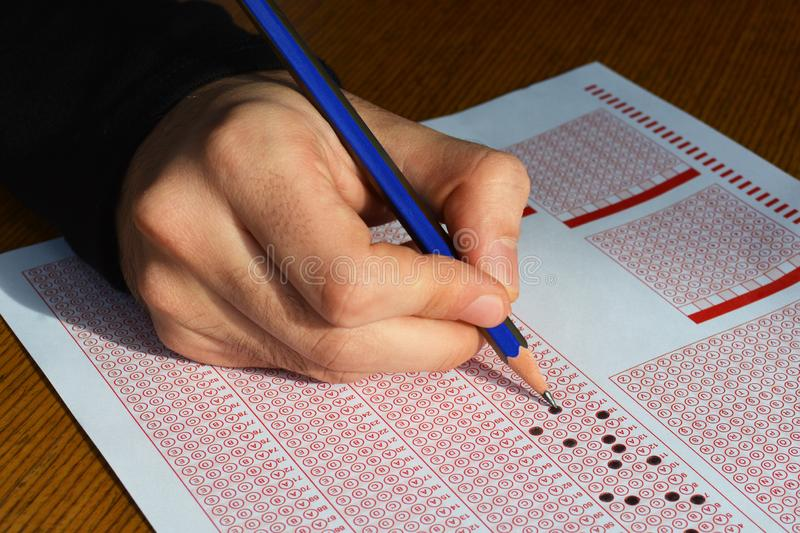 Hand with pencil filling out answers on exam test answer sheet royalty free stock photo