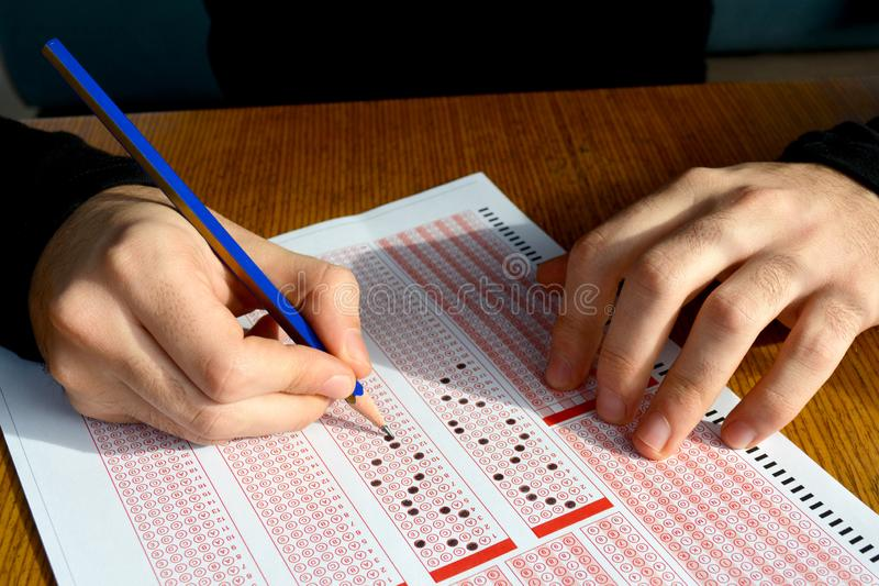 Hand with pencil filling out answers on exam test answer sheet stock photos