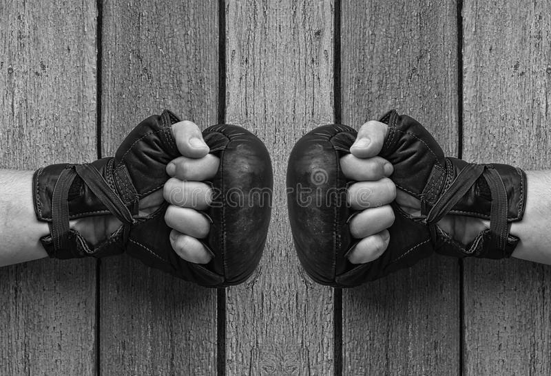 Men hands in black leather gloves for Thai boxing. Clenched on gray worn wooden background, hands opposite each other, black and white toning royalty free stock photos